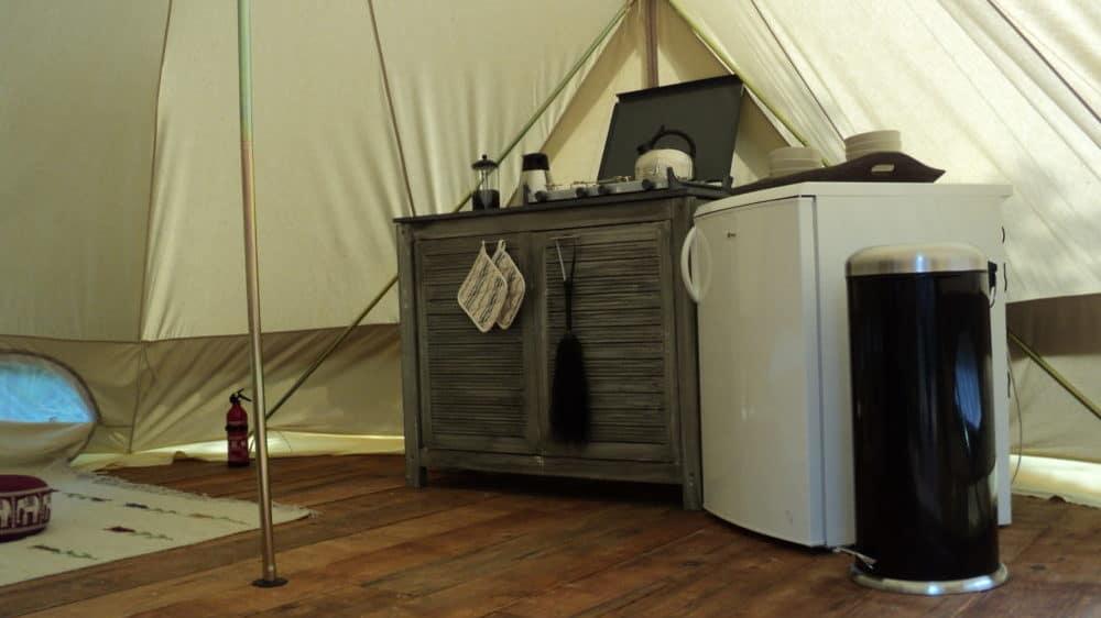 De keuken in de deserttent met koelkast, gasfornuis en keukenkastjes.