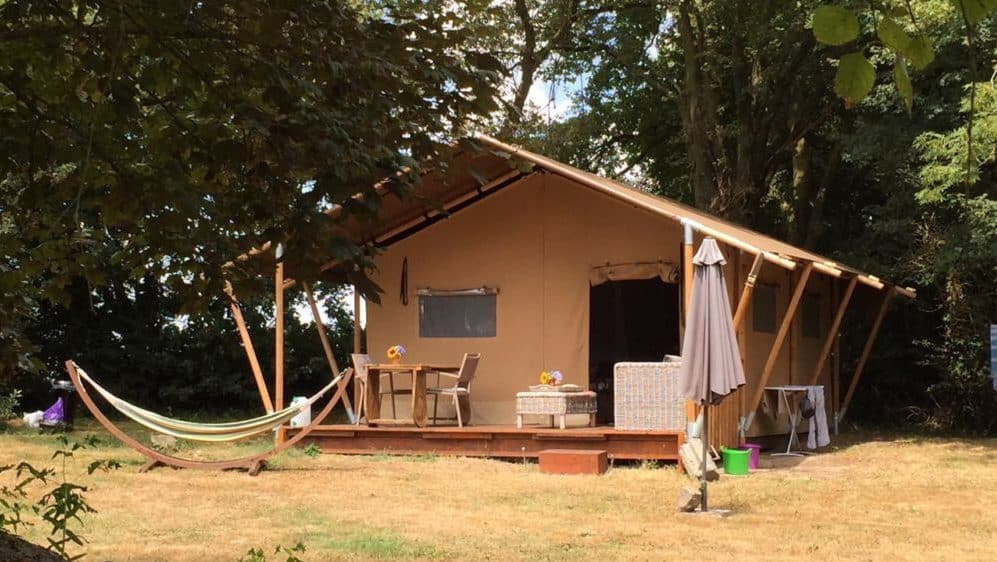 Vooraanzicht van de safaritent, een overdekte vlonder, luie luxe loungebank die uitnodigt tot lekker luieren.