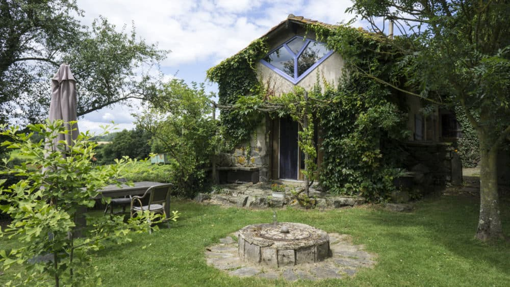 Gite Le Petit Puy, helemaal omgeven door groen en klimop. Lavendelpaarse kozijnen en een waterput van oude stenen op de voorgrond.
