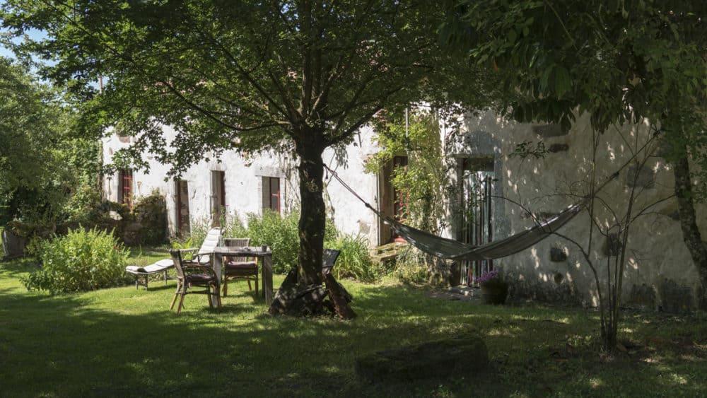 De tuin van de gite Le Rural met hangmat, luie stoel, eettafel en rotan stoelen.