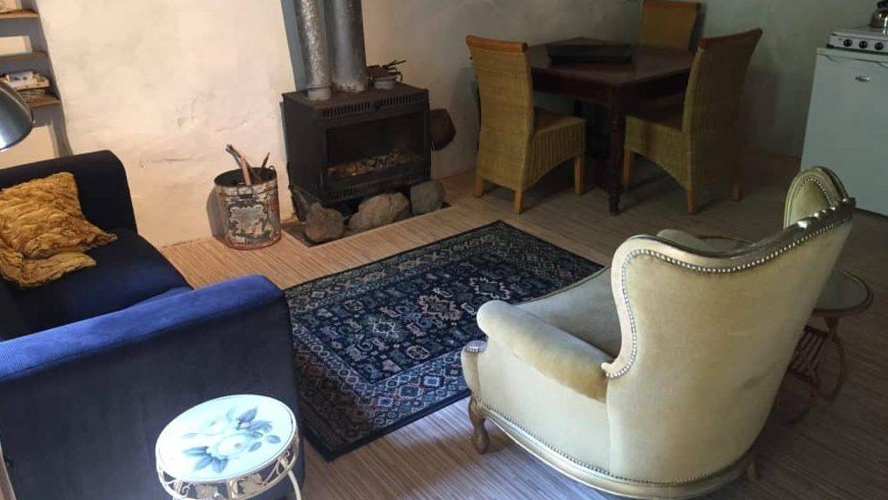 Interieur van gite Le Rural, een houtkachele, donkerblauw vloerkleed, eettafel met 3 stoelen en de keuken met koelkast is nog net te zien.