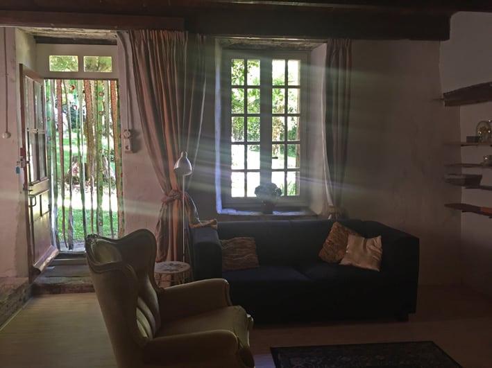 Interieur van de Gite Le Rural, een bankje en Franse stoel. Stralen zonlicht vallen binnen langs de dikke muren van bijna een meter dik. De deur staat open naar de tuin.