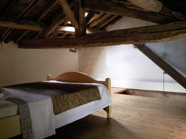 De slaapkamer van gite Le Rural met 2 persoonsbed, mooi opgemaakt. Hele lage balken van het 100-en jaren oude dak.