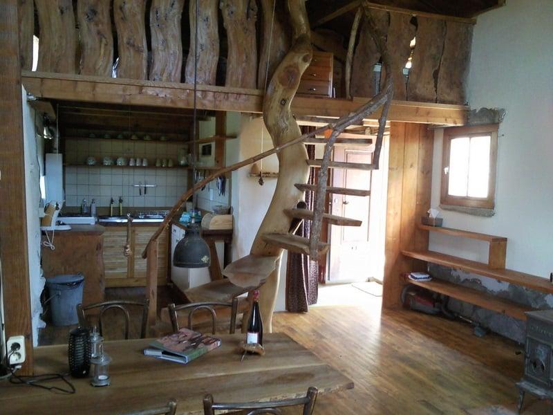 Het interieur van gite Le Petit Puy met een gekronkelde boomtrap naar de slaapverdieping.