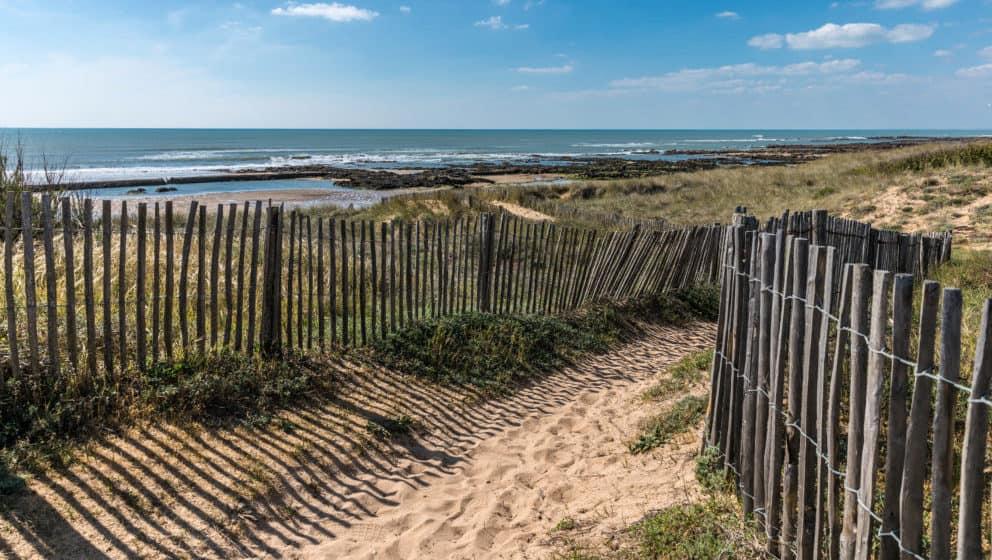 Opgang naar het strand, helmgras, een verweerd hekje en op de achtergrond strand met stenige inhammen.