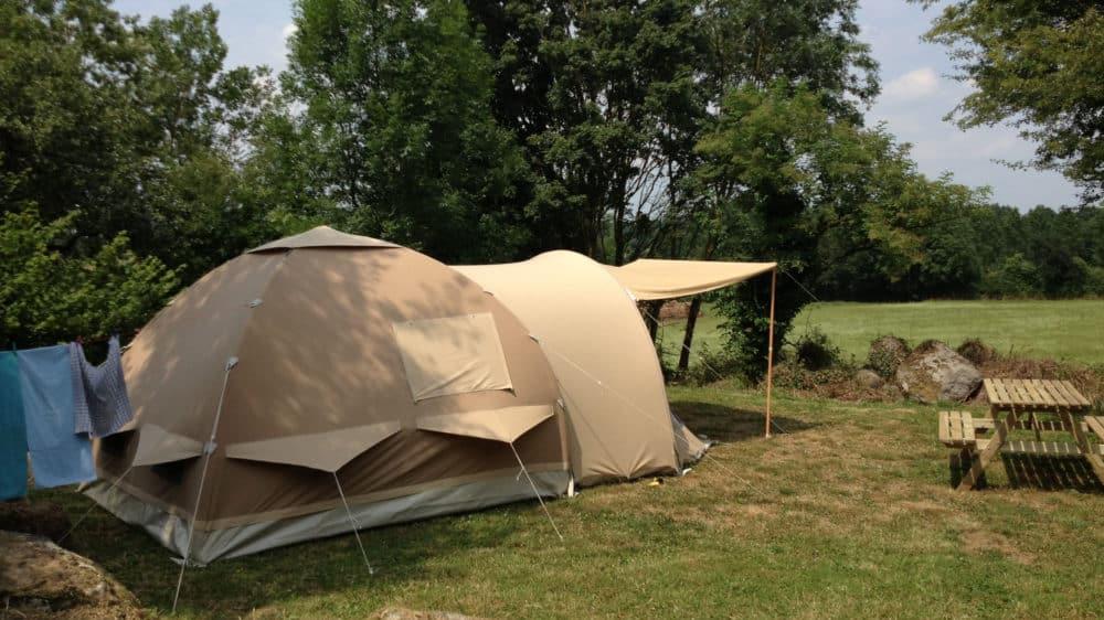 Een gote luxe koepeltent op kampeerplek 1 met wijds uitzicht over het grasland van de buurman. Ernaast een picknick tafel en bank.