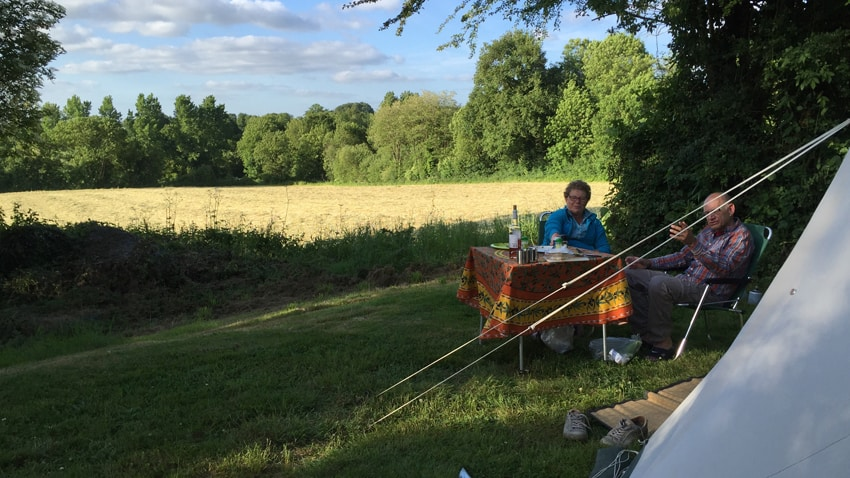 Voor de tent zitten 2 gasten aan een tafelje te eten, flesje rosé erbij. Op de achtergrond een wijds uitzicht met daarachter bomen.