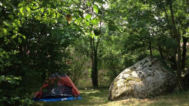Een klein koepeltentje in de schaduw van de bomen met ernaast een enorme granieten steen.