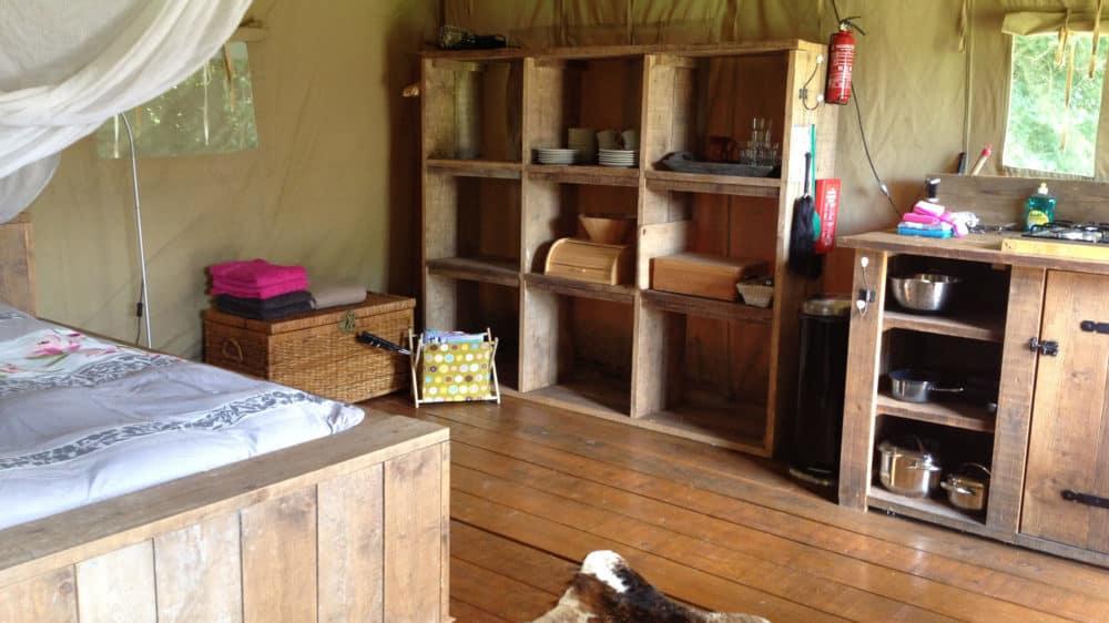 In de safaritent een groot 2persoonsbed met klaboe, een grote vakkenkast met servies en keukenblok met alles er op en er aan.