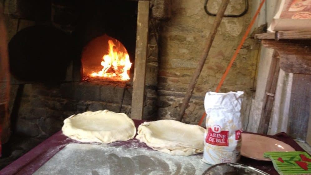 Op de voorgrond, deeg voor pizzabodems, op de achtergrond brandend vuur in de grote oude broodoven.