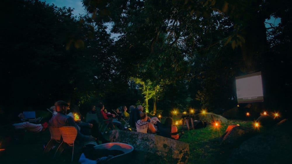 Een sprookjesachtige foto van de film onder de oude kastanjeboom. Een zwoele avond, gekleurde kaarsjes in de schemering, een groep van 20 mensen.